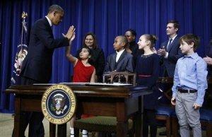 """Le président américain Barack Obama fait un """"high five"""" à une petite fille de 8 huit ans, Hinna Zejah, après avoir dévoilé une série de propositions de contrôle des armes lors d'un événement à la Maison Blanche (Washington), le 16 Janvier 2013. (REUTERS / Jason Reed)"""