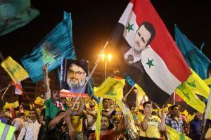 Photo prise durant un rassemblement organisé le 18 juillet 2012 dans la banlieue sud de Beyrouth, pour célébrer les six ans de la guerre de 2006 qui avait opposé l'armée israélienne et le Hezbollah libanais. L'on y voit des supporters du Hezbollah agitant des drapeaux du mouvement chiite et syriens, ainsi que des pancartes à l'effigie du secrétaire général du Hezbollah, Hassan Nasrallah, et du président syrien Bashar al-Assad. Crédits photo : Bilal Hussein/AP