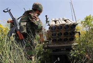 Un combattant du Hezbollah se tenant devant un lance-roquettes multiples (photo : AP)