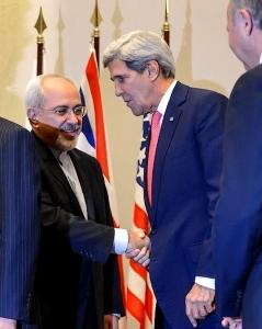 Poignée de main entre le ministre iranien des Affaires étrangères Mohammad Javad Zarif et le secrétaire d'État américain John Kerry, le 24 novembre 2013 à Genève, après  que les cinq membres permanents du Conseil de sécurité de l'ONU et l'Allemagne sont parvenus à un accord intérimaire avec l'Iran sur son programme nucléaire (crédit : Fabrice Coffrini/AFP).