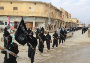 Des combattants de l'État islamique en Irak et au Levant paradant  avec leurs armes dans le district de Tel Abyad, au nord de la Syrie. (Crédit : REUTERS).