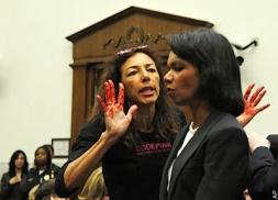 """Le 27 octobre 2007, alors qu'elle s'apprêtait à témoigner devant le Chambre des représentants, la secrétaire d'État Condoleeza Rice fut prise à partie dès son arrivée par une activiste du collectif féminin anti-guerre """"Code Pink"""". Son assaillante, Desiree Anita Ali-Fairooz, tout en agitant ses mains couvertes d'un rouge sang devant le visage de C. Rice, impassible, s'écria : """"vous avez le sang de millions d'Irakiens sur vos mains, vous êtes une criminelle de guerre !"""" (crédit photo: AP)"""
