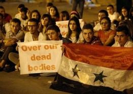 """Sur la photo : des manifestants syriens rassemblés le 13 septembre 2013 à Damas, tenant des banderoles et drapeaux lors d'un sit-in organisé contre le projet d'action militaire américaine. (crédit : AFP - Anwar Amro). Le revirement de Washington a eu un effet psychologique majeur au Moyen-Orient, dont il n'a fait qu'accentuer les divisions. D'aucuns arguant qu'un problème de crédibilité se pose désormais et ses effets se font sentir, notamment dans la manière dont la Russie a agi en Ukraine, sans craindre le camp atlantiste. Les pays arabes du Golfe anti-Damas ont été les premiers à exprimer leur mécontentement contre une décision ressentie comme un """"trahison de la communauté internationale envers la rébellion syrienne"""" (selon les mots de prince héritier d'Arabie saoudite Salmane Ben Abdel Aziz""""). Cette """"perte de crédibilité"""" est présentée comme l'un des signes qui annonceraient le début du déclin du leadership américain global."""